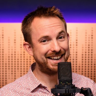 Mike Russel smiling in front of a microphone