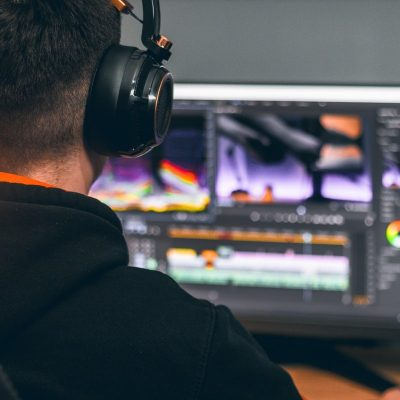 Person with headphones working on Adobe Software