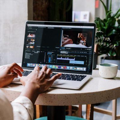 brown hands editing at laptop