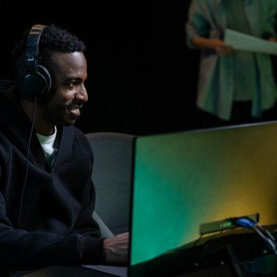 black man with headphones at computer dark tone
